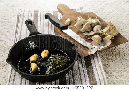 fresh garlic and garlic with olive oil and thyme in a cast iron pan