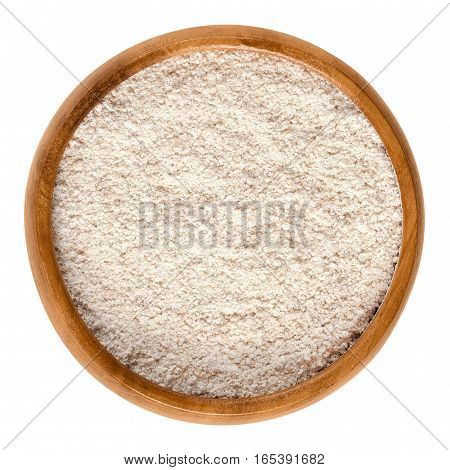 Whole-wheat flour in wooden bowl. Wholemeal flour, a powdery substance and basic food ingredient, made by grinding whole grain of wheat, the wheatberry. Isolated macro food photo close up over white.