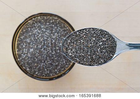 Closeup of spoonful of organic chia seeds.