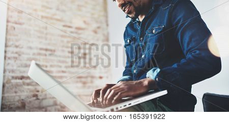 Bearded young African man smiling and using laptop while sitting at his modern coworking place. Concept of happy business people. Blurred background, flare effect, crop