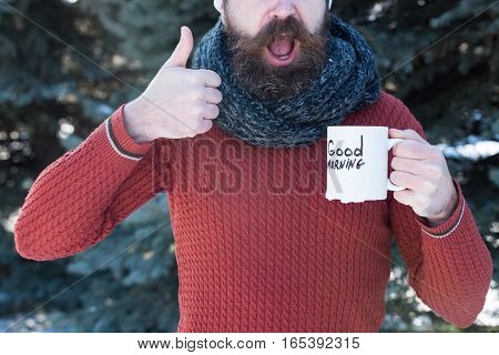 Cheerful handsome man bearded hipster with beard and moustache gives thumbs up hand gesture with good morning text on cup on winter day outdoors on natural background