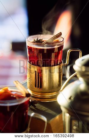 Glass of delicious cherry glintwein thread with cinnamon on vintage background