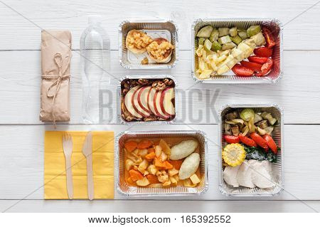 Healthy restaurant food. Chef prepared diet daily meals delivery. Fitness nutrition, vegetables, meat and fruits in foil boxes, water and package. Top view, flat lay on white wood with copy space