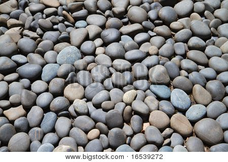 Large bed of gray and dark blue smooth river rock
