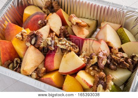 Healthy eating, diet concept. Healthy lunch, dessert. Take away organic food. Weight loss diet, take away in foil box. Healthy food. Apple and pea with walnuts dessert, closeup