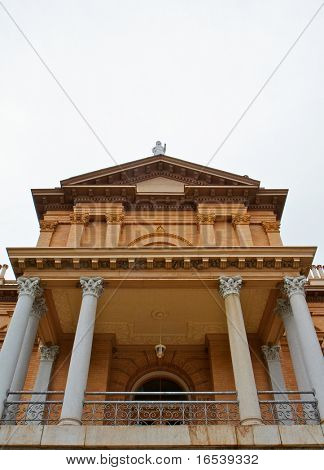 Front facade of pillared tan brick courthouse with statue on top poster