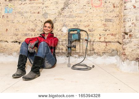Ambitious Craftswoman Sitting On Floor In Front Of Brick Wall In Bare Brickwork With Caulking Hammer