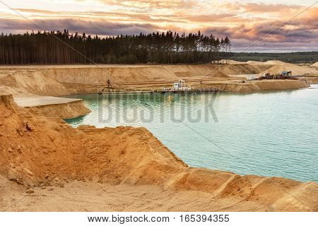 Sand Quarry With Blue Lake Under The Magnificient Sky.