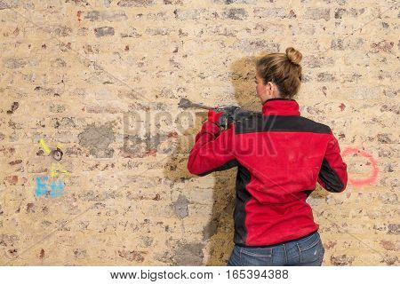 Ambitious Craftswoman With Caulking Hammer In Front Of Brick Wall In Bare Brickwork