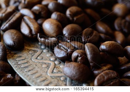 Closeup of coffee beans on vintage metal dish with geometrical ornament, food background with horizontal composition