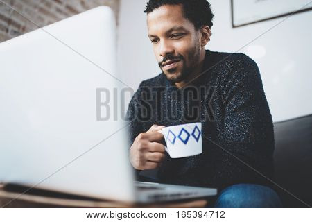 Cheerful African man using computer and smiling while sitting on the sofa.Black guy holding ceramic coffee cup in hand. Concept of young business people working at home. Blurred background