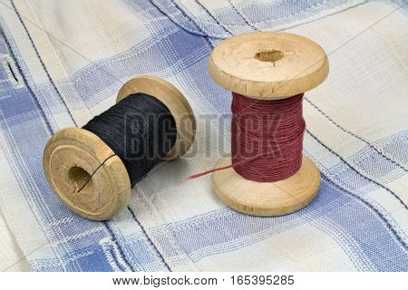 Thread on the wooden spools on a fabric background