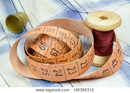 The tailor's tape measure a wooden spool of thread and thimble on the fabric