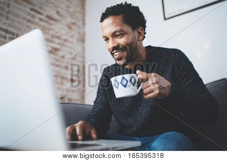 Cheerful African man using computer and smiling while sitting on the sofa. Black guy holding ceramic coffee cup in hand. Concept of young business people working at home. Blurred background. Selective focus