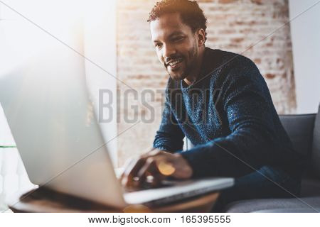 Cheerful African man using computer and smiling while sitting on the sofa. Concept of young business people working at home. Blurred background, flares