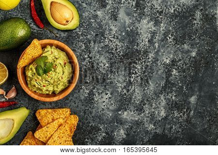 Homemade guacamole with nachos top view copy space.