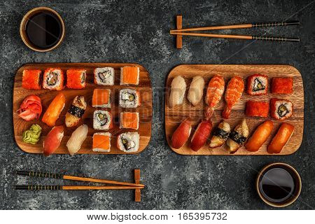 Sushi Set: sushi and sushi rolls on wooden plate top view.