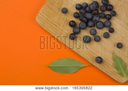 Fresh Blueberry on wooden table over orange background