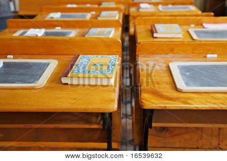 Two rows of  old school house wood desks with chalk tablets and reading books
