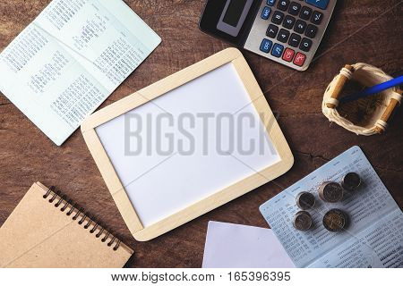 Blank whiteboard with calculator. Passbook blank paper and coins on wooden table for mocup display planning Money Financial Accounting Concept