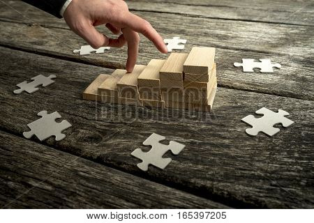 Fingers of businessman walking fingers up blocks arranged in upward trend graph with scattered jigsaw pieces.