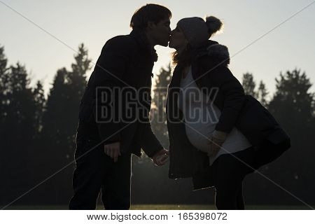 Pregnant woman kissing partner outdoors viewed in silhouette with trees in background.