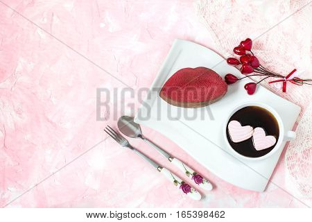 Festive dessert: red velvet cake in form of a kiss and coffee with hearts of marshmallow on delicate pink background with space for text. Sweet treat for romantic date or breakfast on Valentines Day
