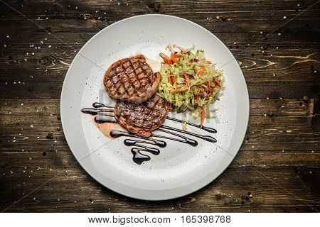 Grilled pork dish with fresh vegetables and spices. Food photography of grilled pork medallions with herbs and spices. Tasty cook meat with vegetables on dark wooden background