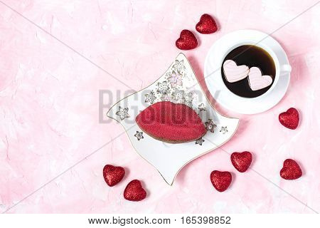 Festive dessert: red velvet cake in form of a kiss and coffee with hearts of marshmallow on delicate pink background with space for text. Sweet treat for romantic date or breakfast on Valentine's Day
