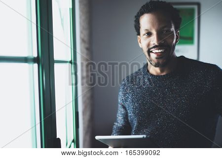Selective focus. Smiling bearded African man looking at camera and holding in hand digital tablet near the window in apartment. Concept of young business people working at home. Blurred background.