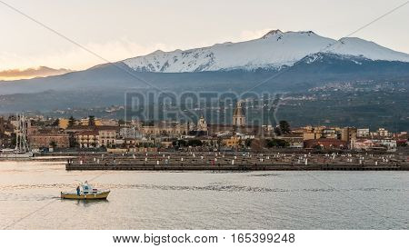 The marina of Riposto during the sunset; volcano Etna in the background