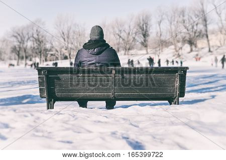 Man sitting on bench looking at people ice skating