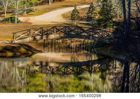 ARTSY SCENE OF A FOOTBRIDGE AND DIRT ROAD WITH REFLECTIONS IN A POND