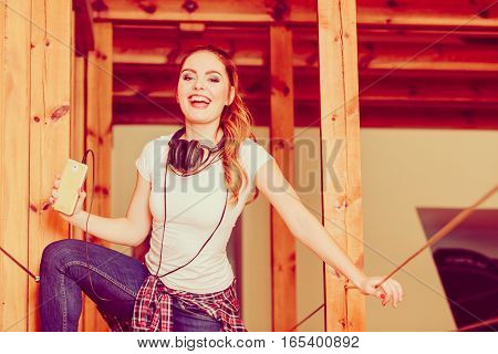 Hobby music expression and free time. Young girl listen music on phone dance indoors have fun hold smartphone.