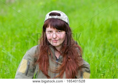 scout girl in military jacket. in emotions from green nature