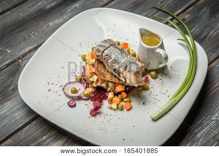 vegetable salad with herring with olive oil on wooden background.