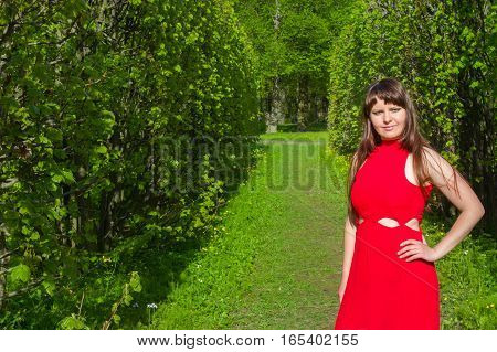 Redhead girl with magnificent forms in red outfit during photo shoot outside city in parkland