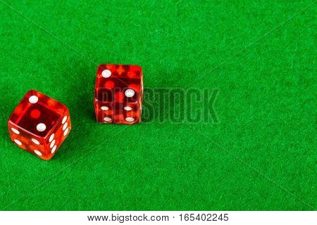 Two gambling dice on a card table showing double 2
