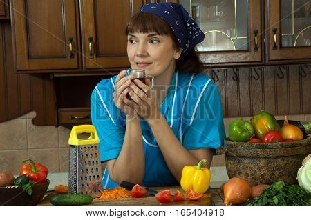 Woman drinking tea in the kitchen among the vegetables