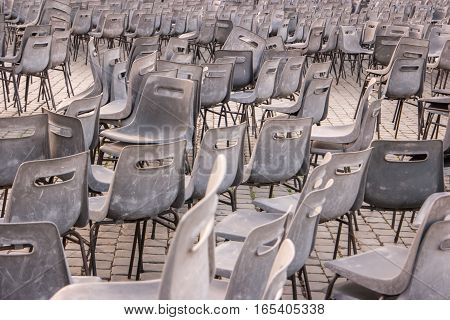 Many gray chairs. Plastic chairs outdoor. Town square after concert.