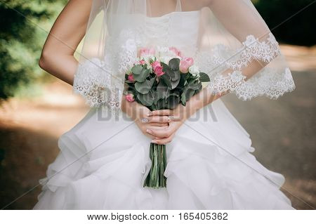 Bride boho style. Those girls are not seen are only visible hand with a bouquet and a long white dress. Bouquet of peach roses. The girl flowing white dress photographed in nature.