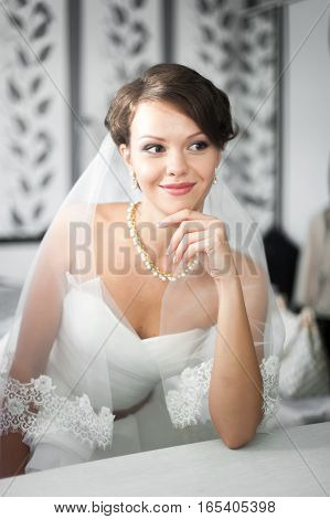 Portrait of beautiful bride with fashion veil posing at home at wedding morning. Makeup. Blondegirl with elegant hair styling. Wedding dress.