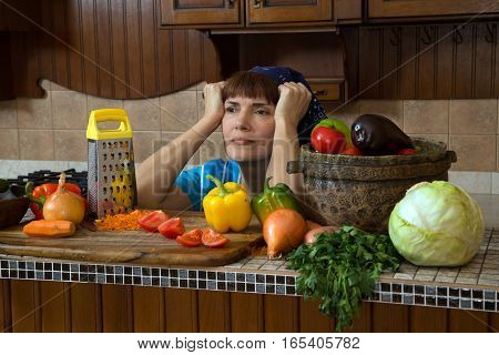 tired woman in kitchen among different vegetables