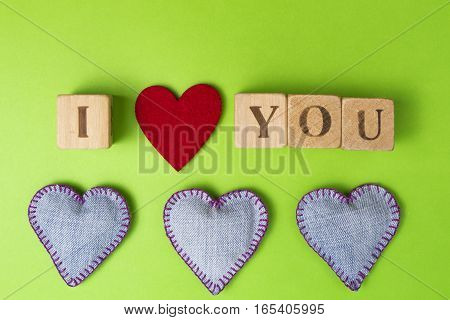 Rustic alphabet blocks that spell out I Love You and Valentine hearts of jeans on greenery background. Top view. Copy space for text.
