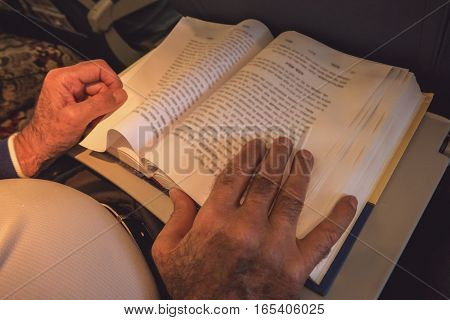 Male hands and opened book. Pages with text. Source of wisdom.