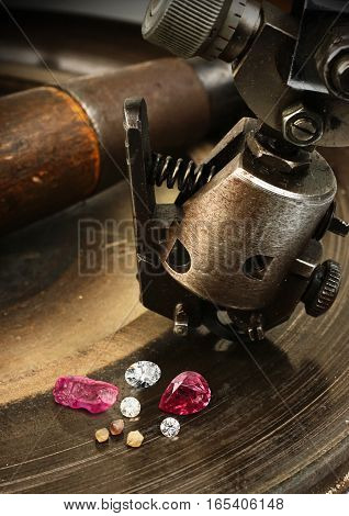 Faceting gemston big diamond with jewelery equipment on background.