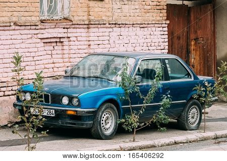 Tbilisi, Georgia - October 21, 2016: Old rusty sedan car BMW 3 Series E30 parking on street. The BMW E30 is an entry-level luxury car which was produced by BMW from 1982 to 1994.