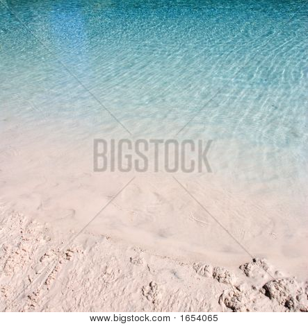 Blue Water Ripples On A Sandy Beach