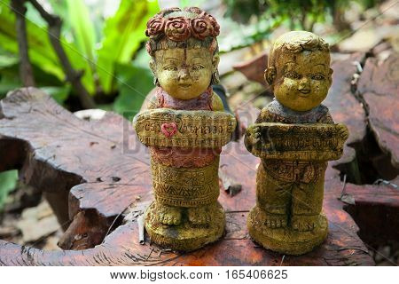 stone figurines on a wooden board in the garden