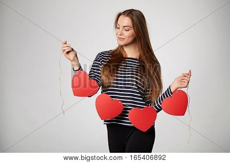 Beautiful smiling woman holding garland of four red paper hearts shape - blank copy space for letters or text, looking down at hearts